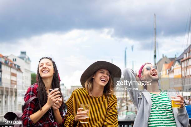 group of happy people drinking beers in nyhavn copenhagen - saturday stock photos and pictures
