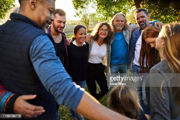 group of happy people embracing on a garden party at sunset - zusammenhalt stock-fotos und bilder