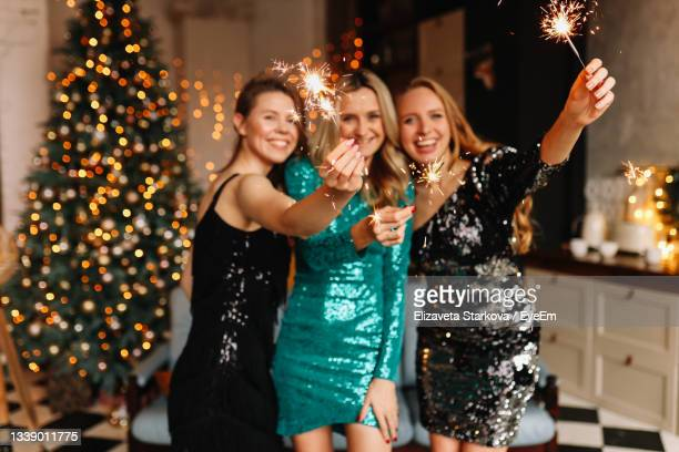 a group of happy people girls friends are having fun at a christmas party in a cozy decorated house - embellished dress stock pictures, royalty-free photos & images