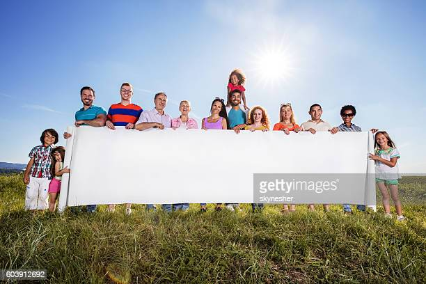 Group of happy people holding big blank banner in nature.