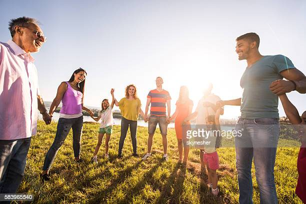Group of happy people holding hands and having fun outdoors.