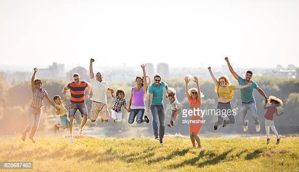 Group of happy people jumping in nature with hands raised.