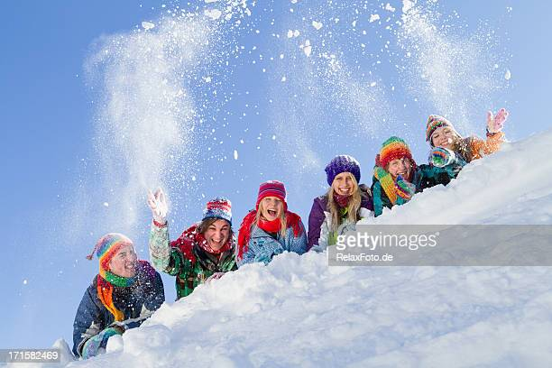 Group of happy people lying on hill playing with snow