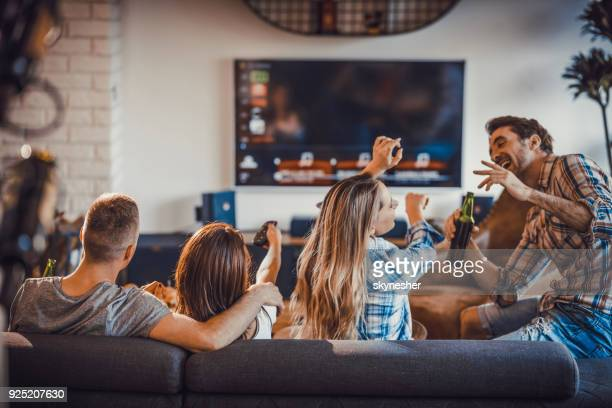 group of happy people spending their time in the living room. - guardare con attenzione foto e immagini stock