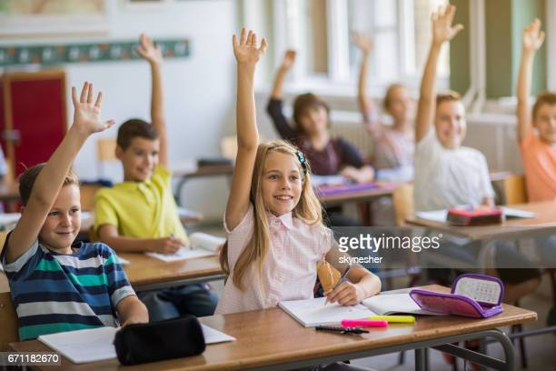 Gruppe der glückliche Schulkinder mit erhobenen Armen im Klassenzimmer.