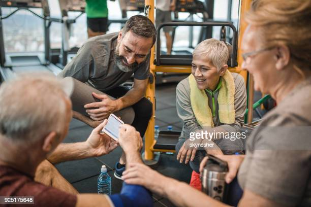 group of happy senior friends using smart phone in a health club. - net sports equipment stock pictures, royalty-free photos & images