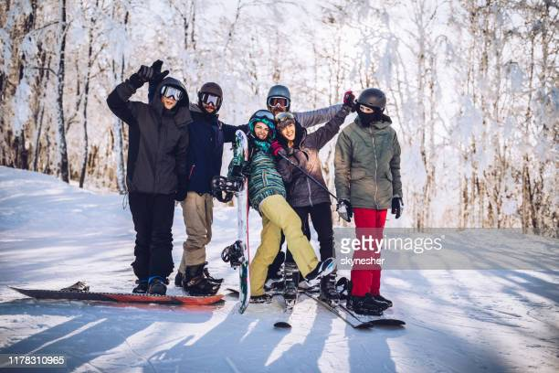 group of happy skiers and snowboarders on a mountain. - boarding stock pictures, royalty-free photos & images