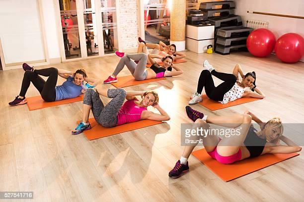 Eine Gruppe von glücklichen Frauen machen sit-ups auf Sport-training.