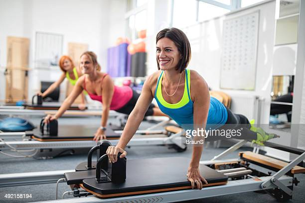 Group of happy women exercising on Pilates machine.