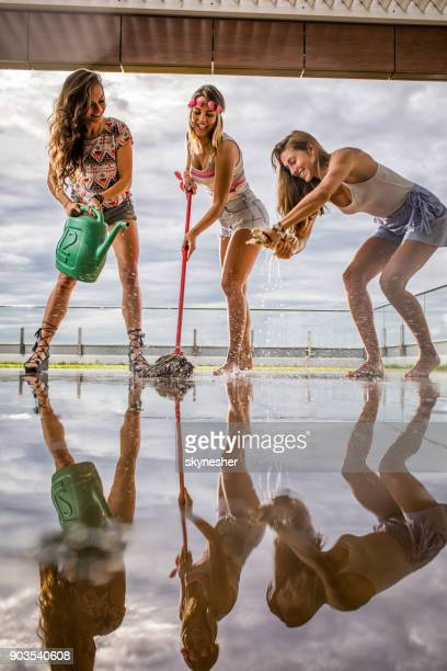 Gruppe von glücklichen Frauen, die Spaß beim Putzen nassen Boden auf der Terrasse.