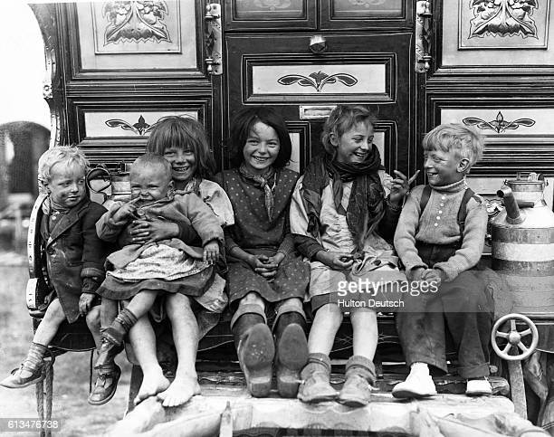 A group of happy young childen seated on the step of a caravan