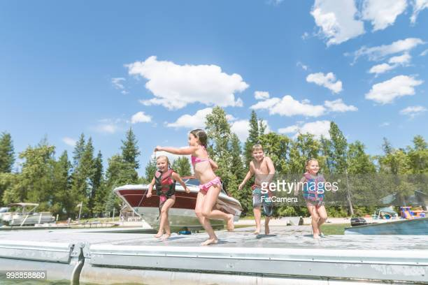 A group of happy young kids in swimsuits run off a dock and leap into the lake