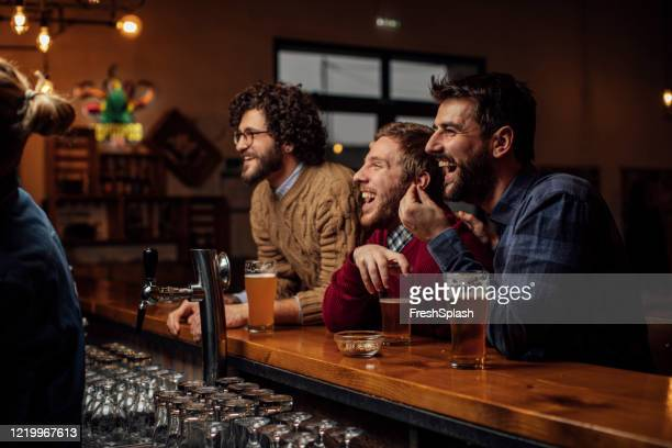 group of happy young men drinking beer and watching a soccer game at the pub - match sport stock pictures, royalty-free photos & images