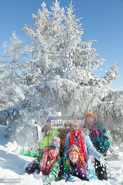 group of happy young people lying in snow throwing snowballs - apres ski stock pictures, royalty-free photos & images