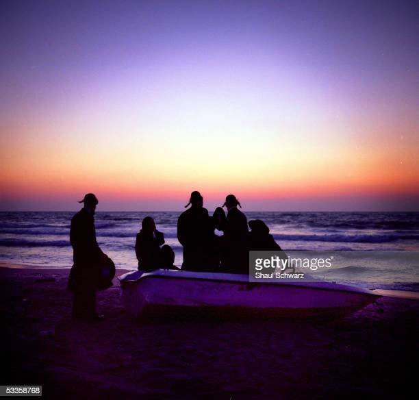 USA*** A group of Hasidic Orthodox men sits on an abounded boat on the beach to watch the sun set May 9 2005 in the settlement of Shirat Hyam in Gush...