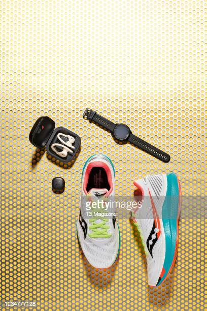 Group of health and fitness gadgets designed to assist running, including Beats Powerbeats Pro headphones, Garmin Forerunner 745 sports watch, Zwift...