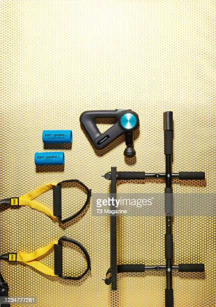 Group of health and fitness gadgets designed to help build muscle, including a pair of MyProtein Fat Gripz, Theragun PRO, TRX Home 2 suspension...