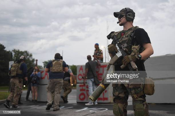 """Group of heavily armed men who identified themselves as the """"People's Protection Group"""" arrive during a protest outside the police department on June..."""