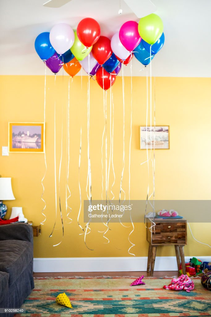 Group Of Helium Balloons With Strings Hanging Down In Living Room ...