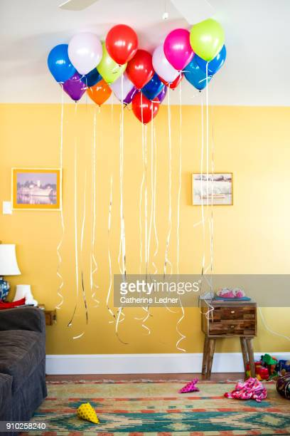 Group of helium balloons with strings hanging down in living room with yellow wall