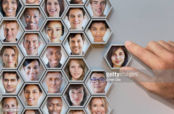 group of hexagonal portrait pods, hand adding one - diverse community stock pictures, royalty-free photos & images