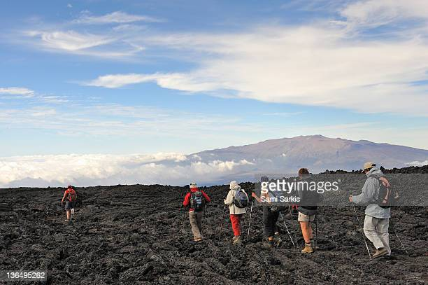 Group of hickers walking on cooled lava