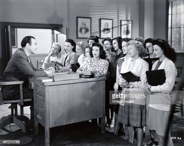 A group of high school girls confront a male teacher in a scene from a film circa 1940