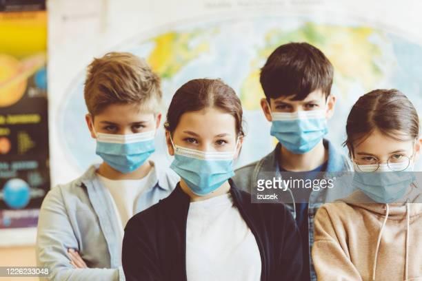 grupo de estudantes do ensino médio na escola usando máscaras faciais n95 - izusek - fotografias e filmes do acervo
