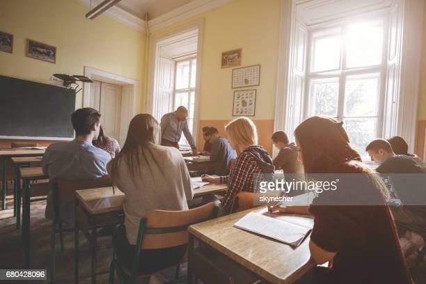 Groep van middelbare scholieren leren in de klas.