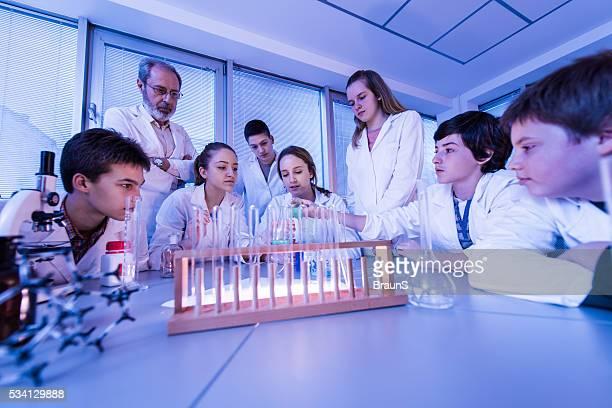 Groupe de lycéens étudiants dans un cours de chimie.