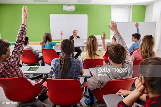 Groupe de lycéens étudiants mettre leurs mains de la classe.