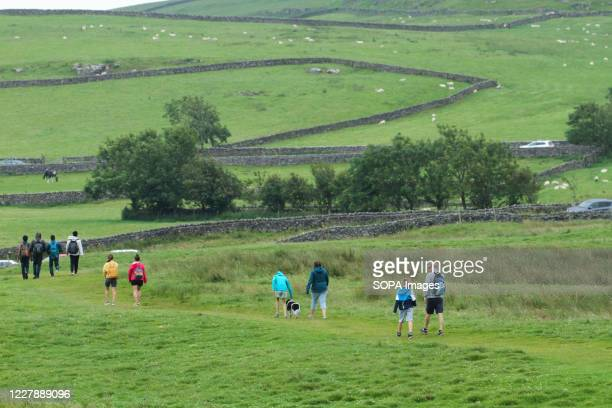 Group of hikers climb down a hill on Hope Valley in the Peak district. With the predicted warm weather, people ventured outdoors amidst the novel...