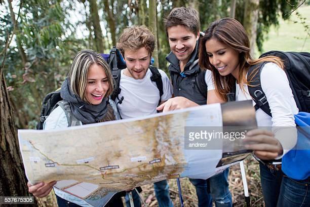 Gruppe von Wanderern hält eine Karte und finden Sie Ihren Weg
