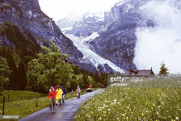 Hikers Pass by the Glacier on a Foggy, Rainy Day