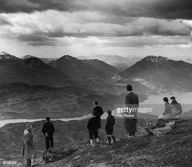 Group of hikers scale Ben Lomond in Scotland, to gaze down at the Loch below.