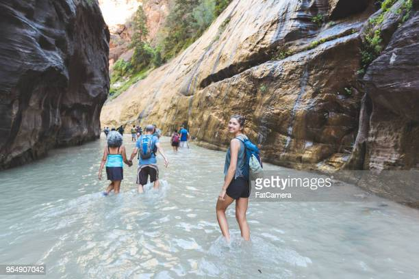 Group of hikers wade through water in a slot canyon