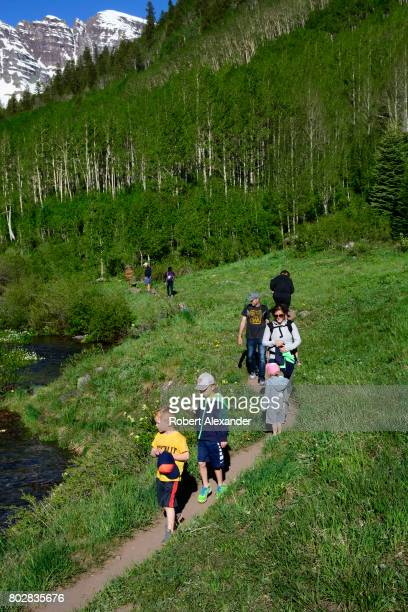 A group of hikers walk beside Maroon Creek with the Maroon Bells in the background The Maroon Bells near Aspen Colorado are two peaks in the Elk...
