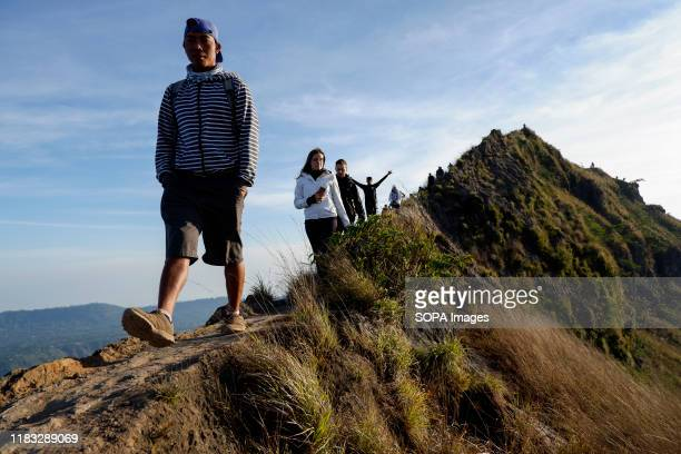 A group of hikers walk the trail at the summit of Mount Batur in Bali during the sunrise A popular tourist destination Mount Batur is a 1717 meter...