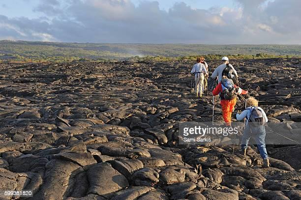 group of hikers walking on cooled pahoehoe lava flow at sunrise, kilauea volcano, big island, hawaii islands, usa - ハワイ火山国立公園 ストックフォトと画像