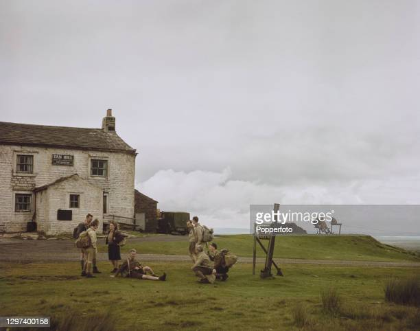 Group of hikers walking the Pennine Way path stop to rest outside the Tan Hill Inn, the highest pub in the British Isles, during a walk through North...