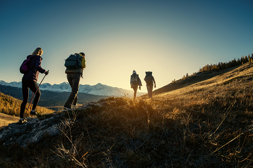 Group of hikers walks in mountains at sunset 1189969126