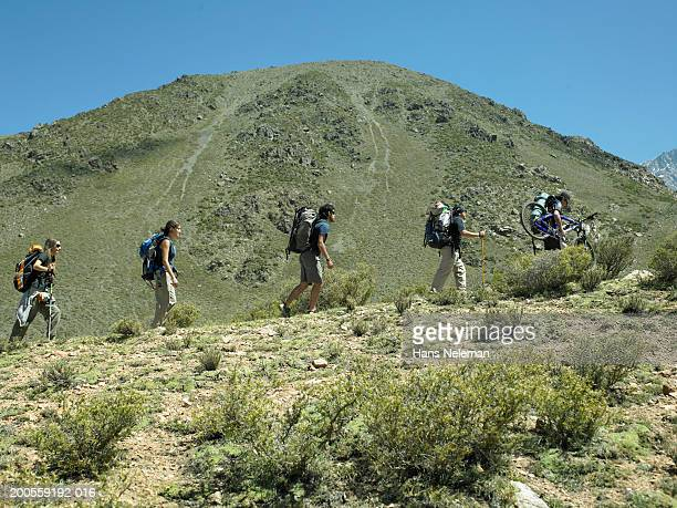 Group of hikers with backpacks and mountain bike, hiking on mountain