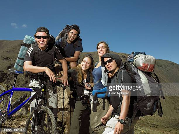 Group of hikers with backpacks and mountain bike, smiling