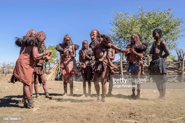 Group of Himba women with traditional dresses dancing in a circle, some of them while carrying their babies on their backs.