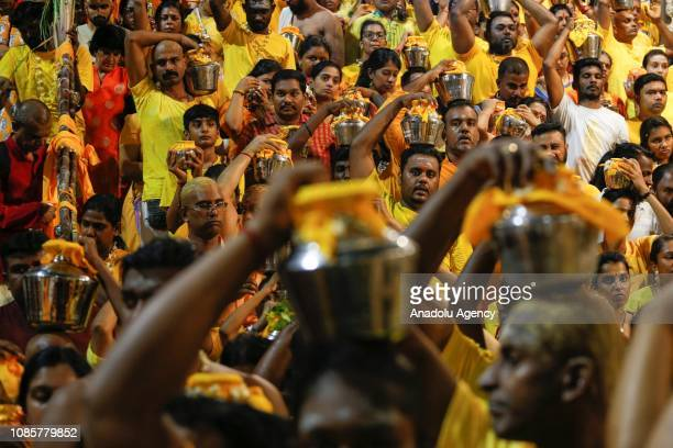 A group of Hindu devotees carry pots of milk on their heads inside the Batu Caves Temple during the festival of Thaipusam in Kuala Lumpur Malaysia on...