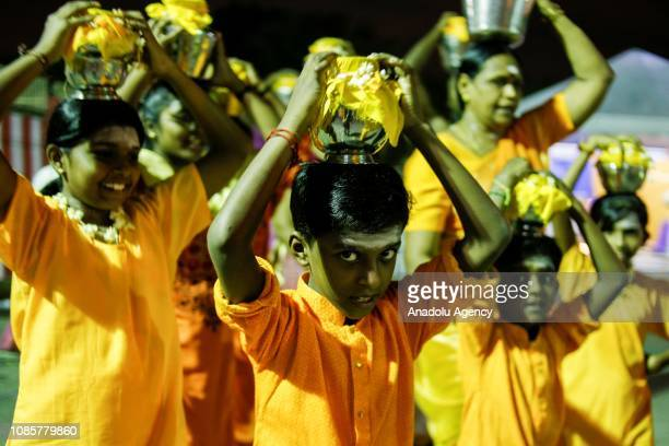A group of Hindu devotees carry pots of milk on their heads prior to walking up to the Batu Caves Temple during the festival of Thaipusam in Kuala...