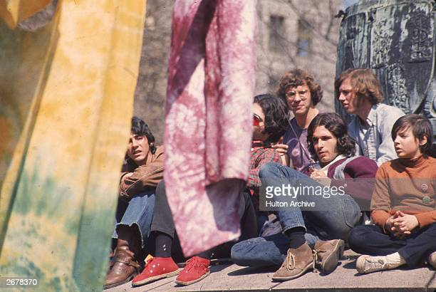 A group of 'hippie' men and children sit in a park with tiedyed tapestries on Earth Day April 22 1970