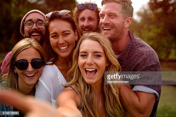 Group of hipster friends taking selfie with stick at sunset