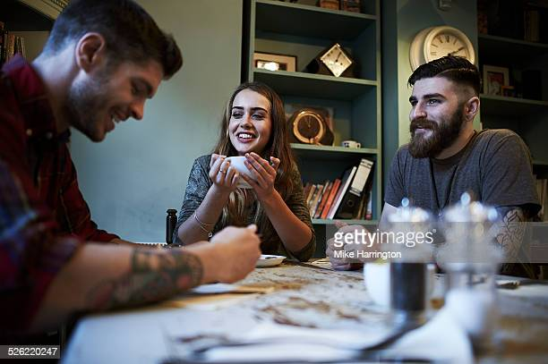 group of hipsters in cafe - small group of people stock pictures, royalty-free photos & images