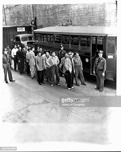 A group of hispanic men dressed in Zoot suits stand chained together as they wait to board a Los Angeles County Sheriffs' bus for a court appearance...